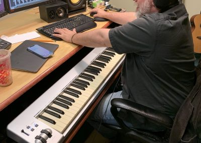 Image from a recording session inside a studio with a man manipulating a computer recording software