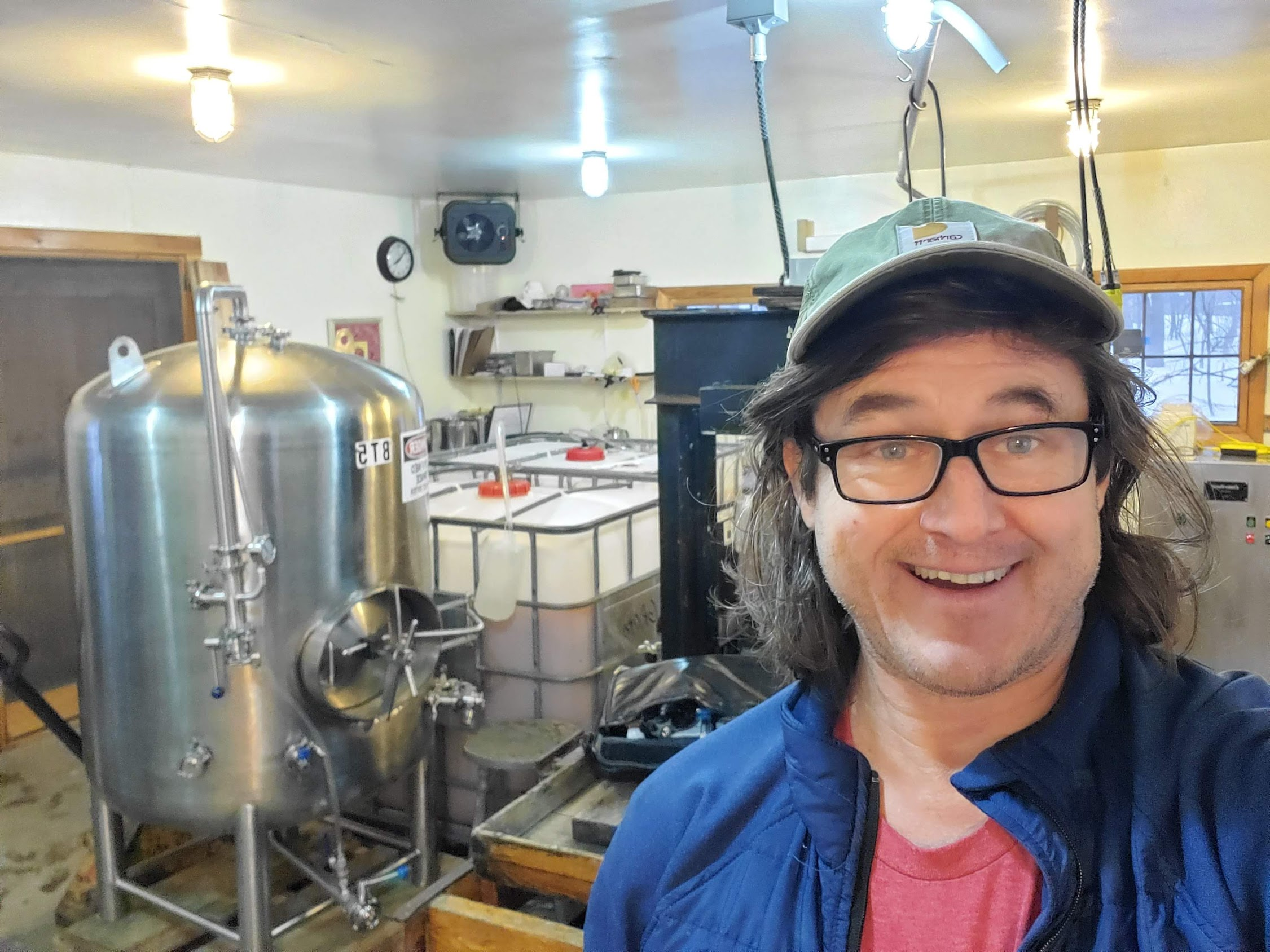 Headshot of Willian Grote, founder of New Salem Cider with cider press and other equipment in the background.