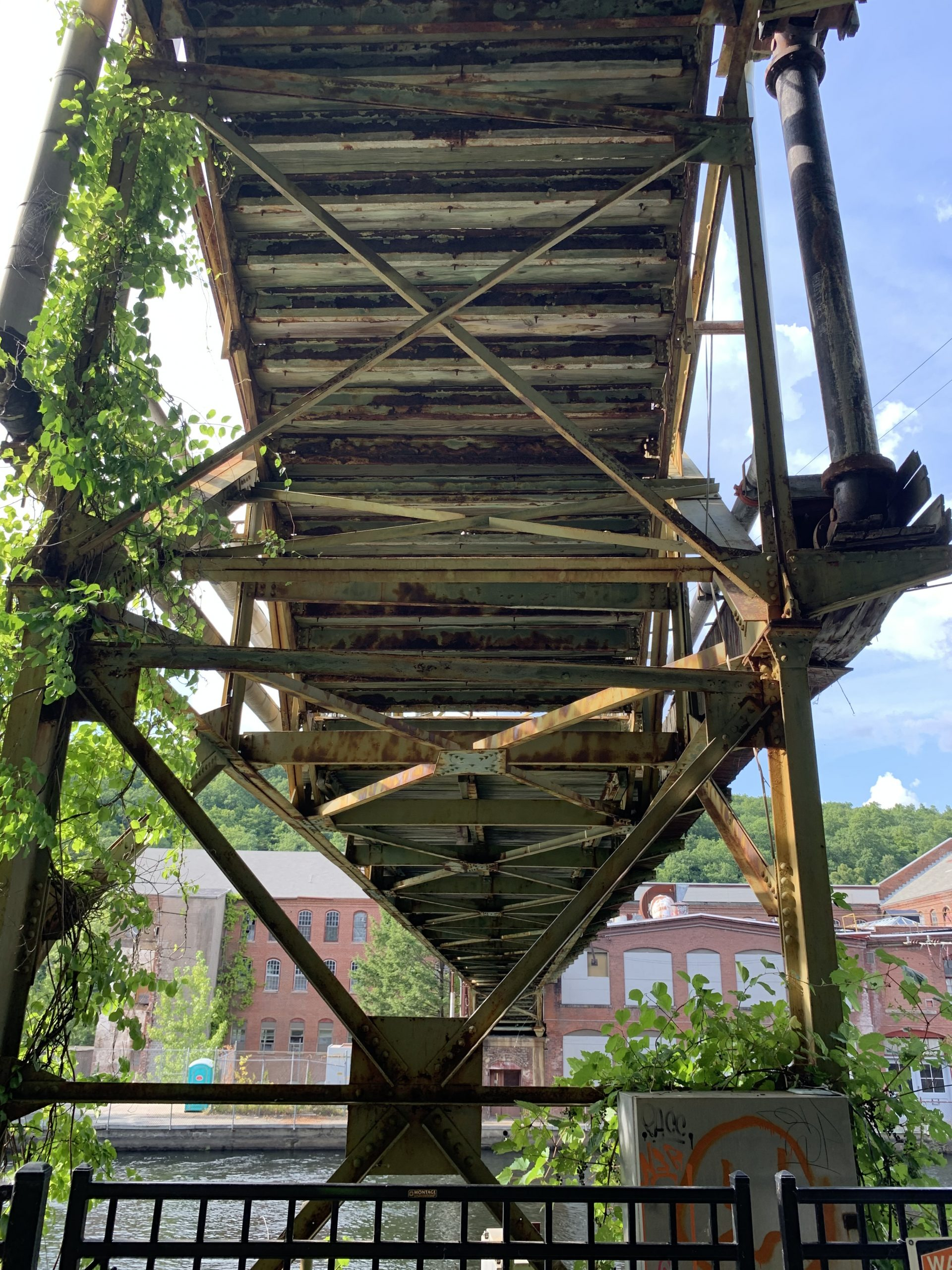 Workers walk bridge, Turners Fall, MA example of post-industrial blight due to ultra-capitalism