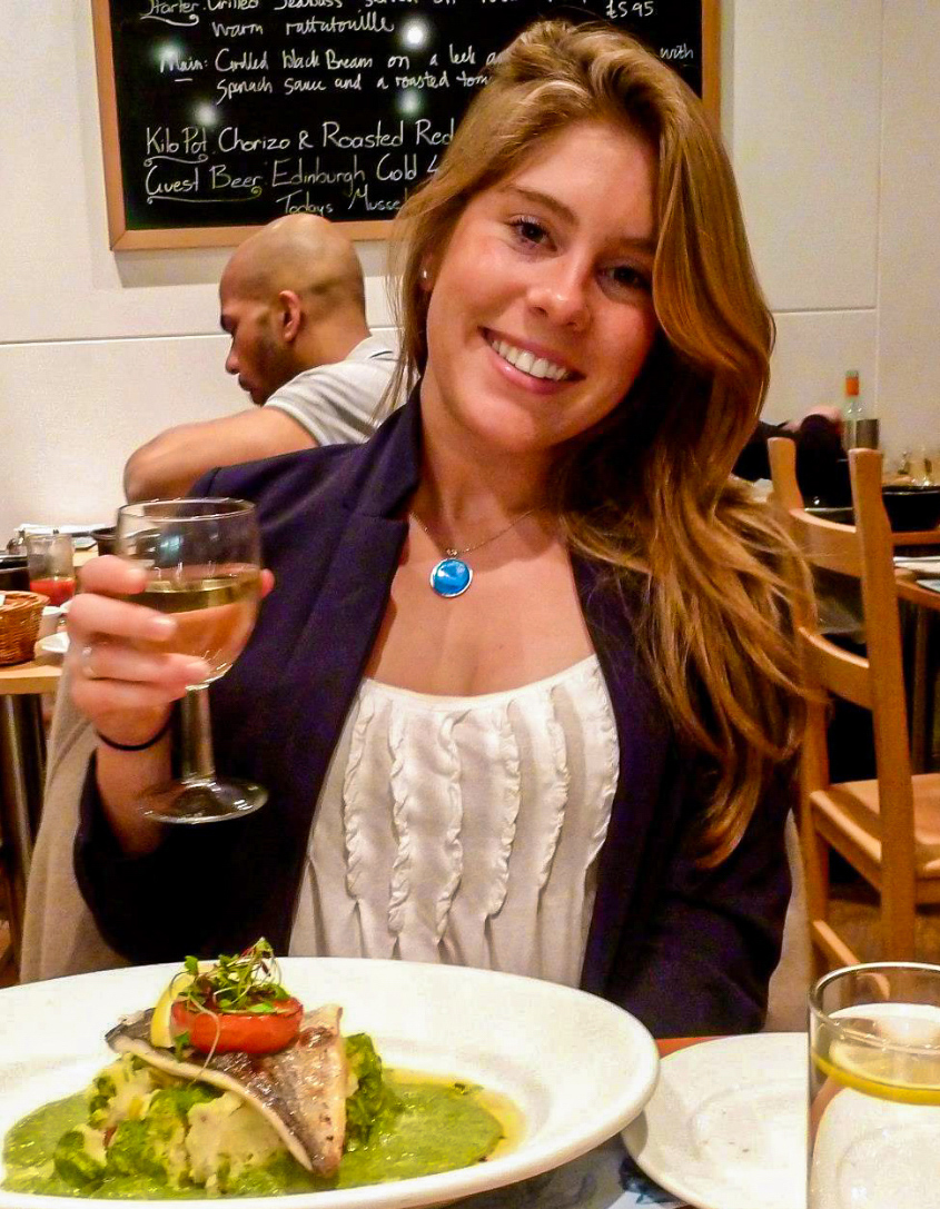 Headshot of Victoria Pardo, Full color, posh dining room in background, elegant meal in foreground and white wine glass in hand.