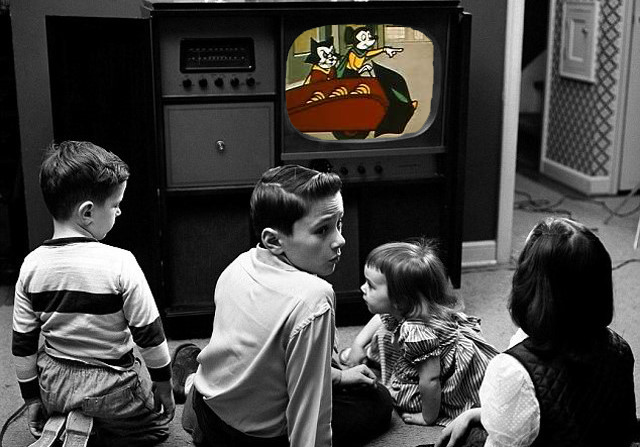 black and white image from circa 1960's of children watching animated cartoons. The cartoons are in full color and rest of image is not.
